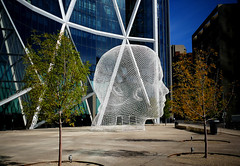 Wonderland Sculpture. Calgary. (Bernard Spragg) Tags: wonderlandcalgary art publicart face bowtower canada calgary downtown lumixfz1000 jaumeplensa