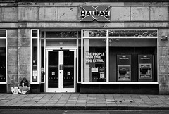 'The people who give you extra?' (Canadapt) Tags: woman homeless beg bank window door sidewalk street juxtaposition irony edinburgh scotland canadapt bw