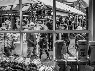 Market shoppers through a shop window in York.
