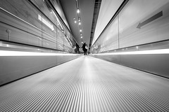 Direction (CoolMcFlash) Tags: bnw bw blackandwhite person candid streetphotography vienna arrow direction leadingline lines escalator sw schwarzweis wien richtung pfeil fluchtpunkt pov pointofview perspective perspektive fujifilm xt2 xf 1024mm f4 r ois modern city stadt
