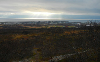 Sunrays above the arctic town and sea