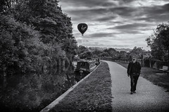 canal travel (Daz Smith) Tags: dazsmith fujixt20 fuji xt20 andwhite bath city streetphotography people candid portrait citylife thecity urban streets uk monochrome blancoynegro blackandwhite mono canal boat towpath balloon hotair man cap walkingwater reflection