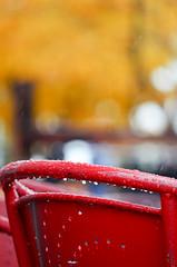 October rain and shine (James_D_Images) Tags: sidewalk cafe red metal chair october 2016 fall autumn sun rain yellow leaves bokeh drops wear spokane washingtonstate
