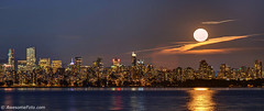99.9% full moon rising above Downtown Vancouver (james c. (vancouver bc)) Tags: waninggibbous america bc purple britishcolumbia canada city cityscape colorful destination evening highrises moon nature pacificnorthwest reflection scene scenery scenic sea sky tourism touristic travel vancouver view westcoast mountain tree autumn fall color colour leaf dusk twilight water downtown skyscraper cloud orange bright skyline beautiful panoramic panorama fullmoon supermoon building background harvest