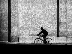 along the wall (Sandy...J) Tags: olympus wall man monochrom street streetphotography silhouette urban blackwhite bw biker light shadow germany lines noir