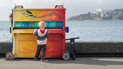 That piano (Dave n Laura) Tags: daveroberts child children kid playing music piano sea water daylight light daytime orange blue red bicycle blonde wellington nz newzealand outdoors keyboard naturallight photo imageoftheday photoofthedaynikonflickraward nikonflickraward playtime play fun musical colorful colourful