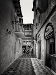 2017-10-14_01-24-30 (GLKPhotos) Tags: street urban people contrast textures lightandshade shadows buildings windows shops balcony walllights tiles mosaic shopfronts doorway glass railings passersby blackandwhite monochrome uncropped salou oldtown spain travel shutters hats sunglasses