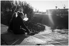 Enjoying the sun (Thomas Wyser) Tags: hamburg deutschland de streetphotography street fujix100f fujifilm people menschen hamburgaltona hamburgerfischmarkt wasser norderelbe elbe hafen schwarzweiss blackandwhite blackandwhitephotography frauen smoke schiffe gegenlicht frontlight