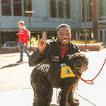 Student poses with therapy dog at Red and White Week Kickoff