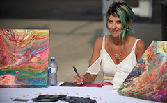 The Artist (Poocher7) Tags: people portrait artist smile female prettygirl lovely greenhair crystalnecklace tattoos whiteblouse art artwork paintings table water pen belmontvillagebestival kitchener ontario canada streetphotography candid