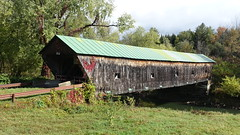 Hammond Covered Bridge over Otter Creek in Pittsford, Vermont.  Built 1842. (lhboudreau) Tags: vermontinthefall bridge coveredbridge hammondcoveredbridge water creek ottercreek pittsford latticetrussbridge vermont outdoor outdoors tree trees grass greenroof windows preservation historicpreservation historic sky wood wooden pittsfordvermont 1842 oldbridge plants shrubs wellworn autumn structure architecture