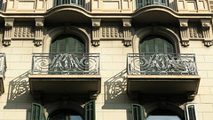 Arches and shadows, Barcelona (Spencer Means) Tags: dwwg balcón balkon balcony window building house apartment shutters closed arch wrought iron ironwork stonework shadow modernista modernisme dreta eixample barcelona catalonia catalunya spain