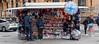 Tourist Kiosk (M C Smith) Tags: kiosk london pentax k3ii people men women car parked silver knickknacks flags umbrellas signs scaffolding building road pavement sales tourist railings minicab pink red blue green bag