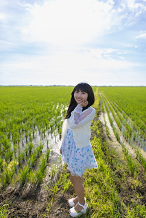 young woman standing in vast rice paddy