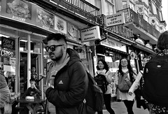 Food If You Want It. (ManOfYorkshire) Tags: chips fishchips takeaway food snack fried lunch meal carton polystyrene tray people oriental feel queensrd brighton group tourists offlicence theargus bw blackwhite eating walking sunglasses