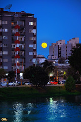 October Harvest Moon (Otacílio Rodrigues) Tags: céu cidade lua moon luacheia fullmoon harvestmoon bloodmoon prédios buildings arquitetura architecture natureza nature urban rio river água water reflexos reflections noite night luzes lights carros cars árvores trees margem riverbank resende brasil oro topf25
