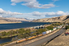 Zipping Through the Gorge (sullivan1985) Tags: unionpacific up ge emd es44ac sd70m intermodal westbound columbiariver biggsjunction deschutesriver freight freighttrain i84 road highway interstate gorge grassland prarie clouds sky americanflag flag up7659 up5032 up5402 zg1br stacks containers armouryellow train railroad railway oregon or pacificnorthwest