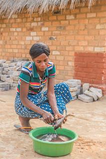 Lucia Chilufya cleaning fish, Zambia. Photo by Chosa Mweemba.