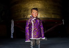 Portrait of a tibetan nomad boy with his cheeks reddened by the harsh weather in front of a prayer wheel in Rongwo monastery, Tongren County, Longwu, China (Eric Lafforgue) Tags: 67years amdo asia asian asianethnicity buddhism china china17579 colourimage day ethnicity frontview horizontal huangnan indoors largegroupofobjects longwu lookingatcamera monastery nomad onechildonly onepersononly people pilgrim pilgrimage placeofworship portrait posing pray prayerwheel qinghaiprovince religion ronggonchen rongpo rongwo spirituality symbolsofpeace tibet tibetan tibetanautonomousprefecture tongren traditionalclothing travel worldtravel