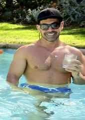 IMG_9557 (danimaniacs) Tags: shirtless hot guy man sexy swimmingpool smile mansolo drink cocktail pecs shorts swimsuit trunks hat cap beard scruff