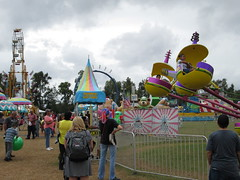 Carnival Rides At The Fair. (dccradio) Tags: lumberton nc northcarolina robesoncounty cloudy overcast bigrockamusements carnival midway fairride amusements amusementdevice mechanicalride ride rides thrillride outdooramusement fun entertainment outdoors outside grass lawn yard lot ground greenery robesonregionalagriculturalfair fair countyfair robesoncountyfair communityevent canon powershot a3400is skywheel doubleferriswheel larsoninternational ringoffire fireball superloops starcommand helicopters spaceship fence ridefence backpack ball people flag flags bearaffair tree trees allenherschell action motion hampton daltonkidsride canopy enter