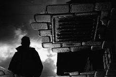 Storm warrior at the rain portal (Mikhail Korolkov) Tags: street reflection silhouette puddle puddlegram grid sky clouds bw blackandwhite monochrome fujifilm xe2 xc50230