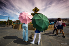 Street - Mother and daughter (François Escriva) Tags: street streetphotography paris france candid people family mother daughter umbrella umbrellas concorde place crillon buildings fountain sky clouds sun light colors pink green blue white ground grey photo rue