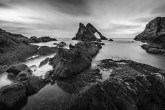 """fine art black & white of natural sea arch of Bow Fiddle Rock, Portnockie, Moray, Scotland (grumpybaldprof) Tags: moray scotland uk """"bowfiddlerock"""" portknockie """"naturalseaarch"""" arch sea """"northsea"""" sandstone quartz tourist seagulls nesting birds port harbour waves rock bow fiddle water sky cloud texture cliff erosion bw blackwhite """"blackwhite"""" """"blackandwhite"""" noireetblanc monochrome """"fineart"""" striking artistic stylistic style contrast shadow bright dark black white illuminated naturalarch northsea light afternoon milky longexposure neutraldensity sigma 1020 1020mm f456 """"sigma1020mmf456dchsm"""" canon 7d """"canon7d"""" wideangle ultrawide"""