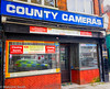 Still Capturing Images (M C Smith) Tags: camera shop bright pentax k3ii countycamera windows shutters signs tiling brown reflections police car pavement blue green red yellow