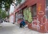 Smoke Break (UrbanphotoZ) Tags: man steps sitting smoking cap graffiti wall redbrick sidewalk warehouse factory ironbars trees fireescape theater pedestrians chinatown manhattan newyorkcity newyork nyc ny