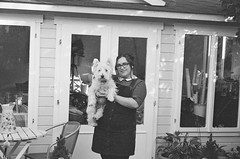 ce650 - chloe and teddy outside the she shed (johnnytakespictures) Tags: canon eos eos650 ilford xp2super expiredfilm expired grain filmgrain 35mm film analogue blackandwhite bw chloelee chloe teddy girl woman dog pet smile smiling pose posing home shed garden glasses spectacles