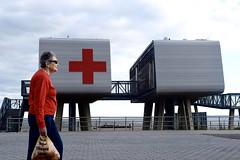 Red Cross Silver Day (-»james•stave«-) Tags: newyork nyc brooklyn city urban brightonbeach coneyisland woman walking color red sweater beach beachfront boardwalk architecture garrisonarchitects buildings two pair modular pavilions elevated stilts redcross lifeguardstation postsandy recovery nikon d5300