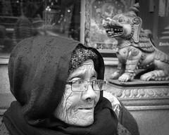 Lady and the lion (posterboy2007) Tags: kathmandu nepal lion statue elderly lady monochrome bw atreet portrait sony