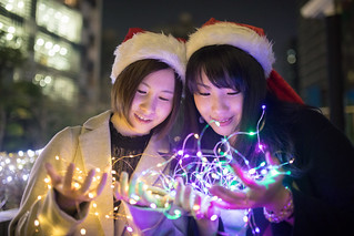 Female friends holding Christmas lights in urban city