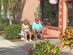 Having a Little Rest (soniaadammurray - Off) Tags: iphone bench exterior people seated epcotcenter florida usa flowers trees shop window signs chairs bushes sidewalk pavement reflections shadows benchmonday rest venice