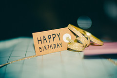 Happy birthday! (*mirt) Tags: birthday macro closeup gift dark wrappingpaper tag bow lint gold glitter bokeh