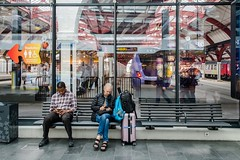 Otherwise occupied (Nodding Pig) Tags: malmö central railway station train skåne sweden concourse passengers 201707086824101