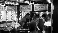 festive market at night 013 (byronv2) Tags: festive festivemarket christmasmarket peoplewatching candid street princesstreet princesstreetgardens edinburgh edimbourg edinburghbynight night nuit nacht blackandwhite blackwhite bw monochrome market mound food cafe foodstall burgers sausages hotdogs cooking eating dining diner