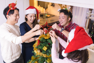 Young friends setting up Christmas tree for home party