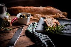Olive bread. (jakub.sulima) Tags: nikon d750 nikkor 50mm 18g food table tableware rustic old interior design wood wooden weathered bread bakedgoods bakery dish snack rosmary olives chili olive oil knife steel ceramic china porcelain restaurant bistro style fall autumn automne herbs studio indoor colours colorful brown gold yellow red black green white grey silver home house homemade plate sheet windowlight dof bokeh noir closeup natur natural