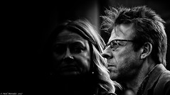 Strangers (Neil. Moralee) Tags: neilmoraleenikond7200 neilmoralee man close face rugged grainy gritty woman dark candid street portrait glasses shadow hair spikey spike profile mature old black white mono monochrome blackandwhite bw bandw strangers faces pair couple hereford england uk neil moralee nikon d7200 mysterious