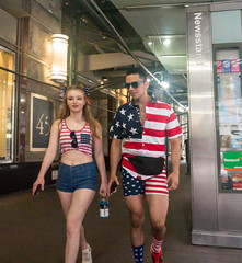 Dressed for the 4th (UrbanphotoZ) Tags: couple americanflag redwhiteandblue shorts shades newsstand passageway financialdistrict downtown manhattan newyorkcity newyork nyc ny patriotic
