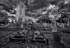 In a haunted graveyard (David Feuerhelm) Tags: nikkor clouds church building tower clock windows roof swavesey cambridgeshire england churchyard cemetery graves gravestones tombstones wideangle contrast blackandwhite noiretblanc schwarzundweiss bw silverefex nikon d750 nikkor1635mm