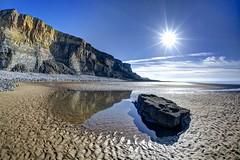 Head first into paradise (pauldunn52) Tags: beach cliffs rock pool glamorgan heritage coast wales traeth mawr reflections sunburst