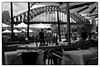 Lunch with a view (cupitt1) Tags: sydney harbour bridge harbourbridge coathanger australia iconic clouds black white monochrome fuji fujixpro1 xpro lunch tables diners cafe view umbrellas street walkers lunchtime crowds