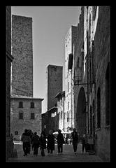 San Gimignano IX (Emilio Casini) Tags: architettura architecture tower torre pietra stone piazza square towers torri sangimignano tuscany italy italia toscana pietre stones persone people street strada bw bn blackwhite bianconero nikonpassion nikon passion noiretblanc