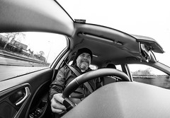 Driver. . . (CWhatPhotos) Tags: cwhatphotos black white mono monochrome drive driver driving olympus omd em5 mkii wooly hat four thirds wide angle fisheye fish eye view samyang prime lens 75mm digital camera photographs photograph pics pictures pic picture image images foto fotos photography artistic that have which with contain artistc art light auto automobile car hyundai i20 hyundaii20 12se 12 se vehicle 2017 new brand inside cab dashboard controls interior man male goatee