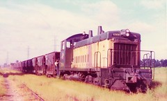 Chicago Northwestern SW1200 locomotives and a string of ore hoppers at Evanston Illinois in 1975 (Tangled Bank) Tags: train trains railway railways railroad railroads old classic heritage vintage chicago northwestern sw1200 locomotive evanston illinois 1975 cnw fallen flag north western
