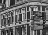 Need a Little Direction (trainmann1) Tags: nikon d7200 nikkor 18200mm amateur handheld november 2017 winter europe amsterdam netherlands honeymoon vacation city capitol outside outdoors exterior buildings windows doors sign facade apartment bw blackwhite desaturated streets brick stone
