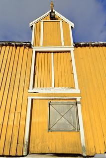 Old yellow port warehouse-closed doors-metal hatch-pulley on top. Nusfjord-Flakstadoya-Lofoten-Norway. 0516